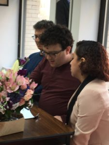 Decision-maker, facilitator, and supporter sit at a table decorated with flowers to read the supported decision-making agreement.